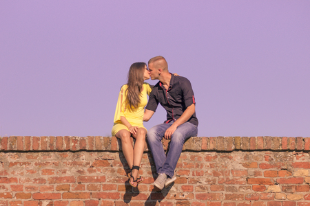 young adult 20s couple kissing sitting brick wall purple sky Stock Photo