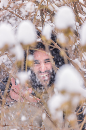 neige qui tombe: one young adult man behind branches, winter cold, happy smiling snow falling
