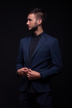 young adult man, 20s model posing, looking sideways, buttoning blue jacket, black shirt, black background studio Stock Photo