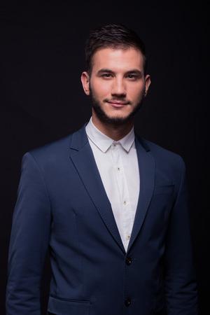 smirking: young adult man, 20s smirking, good looking, white shirt, elegant suit jacket, black background studio Stock Photo