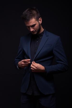 pantalones abajo: young adult man handsome buttoning jacket suit, looking down, black background