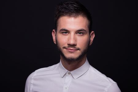 smirking: young adult man man smirking headshot face head portrait white shirt, black background, studio Stock Photo