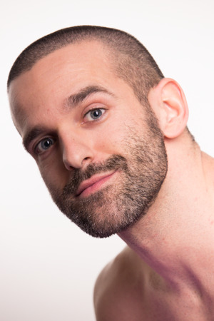 smirking: one young adult man  short hair, head face, white background, shirtless, looking at camera, smirking closeup Stock Photo