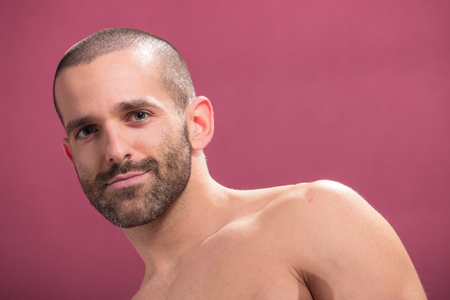 smirking: one young adult man smirking, pink background, shirtless handsome Stock Photo