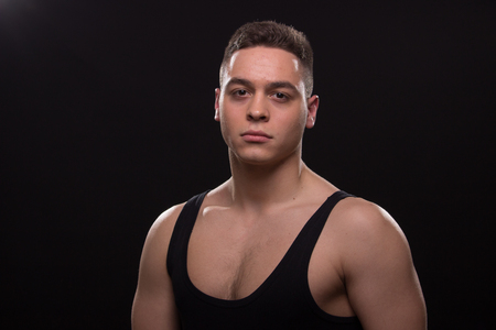 one young adult man tired muscular, good looking, sleeveless t-shirt posing, upper body shot, black background