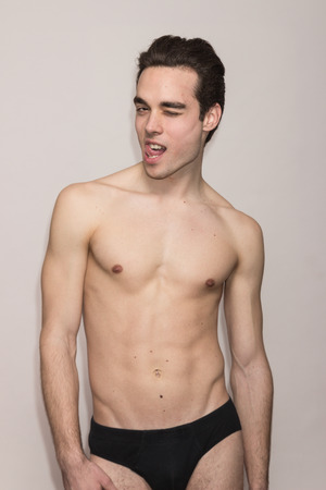out of body: young adult man shirtless body underwear slim fit winking, tongue out, white background