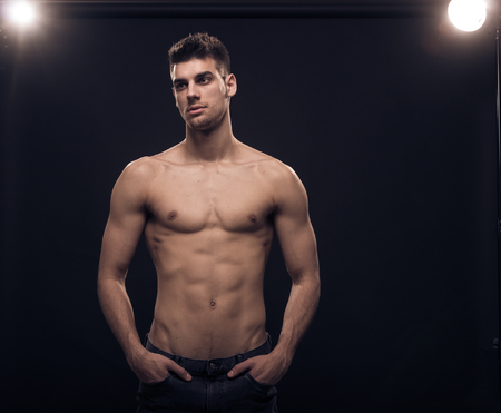 one young man, looking sideways, reflectors shirtless body jeans Banque d'images