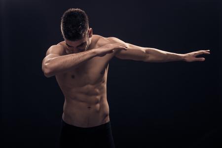 one young man, shirtless body, dub (dance) pose, black background, dark Stock Photo