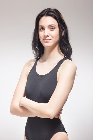 one young woman, standing, blank expression, swimsuit swimmer, arms crossed