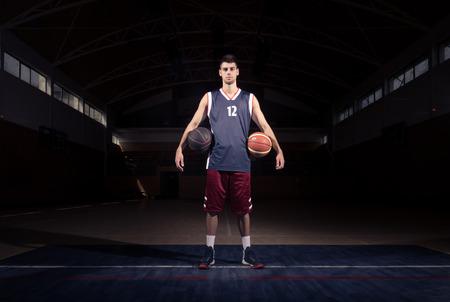 basketball player two balls posing, dark basketball court indoors Stock Photo
