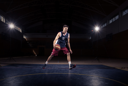 one young adult man, basketball player ball, between the legs dribble, indoors dark basketball court Imagens