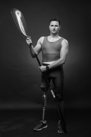 one young adult man only, canoe kayak paddle, athlete sportsman, prosthetic leg, disabled, black and white