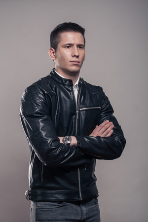 one young adult man only, looking sideways, looking tense, leather jacket, studio, gray background