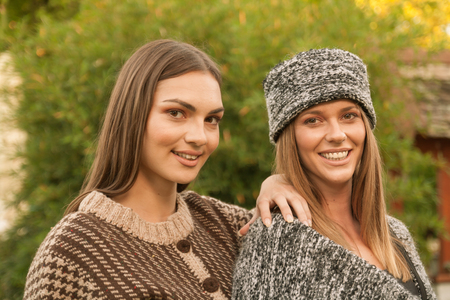 ethno: two young adult Caucasian woman, head and shoulders shot, smiling, looking to camera, wearing Ethno clothes (Serbia, Eastern Europe), hand knit jacket sweater, hat, outdoors