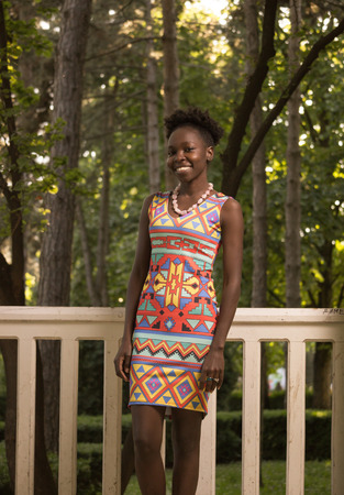 one, young adult, black african american happy smiling woman 20-29 years, standing, looking to camera, outdoors park fence nature, sunny day, wearing dress