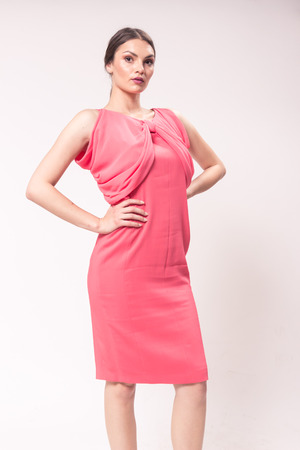 one young Caucasian woman 20s, 20-29 years, fashion model posing standing, studio, white background, fashionable pink dress, looking to camera