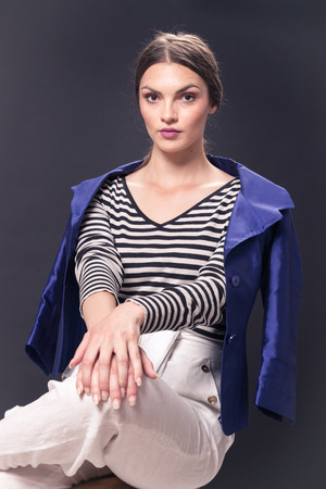 one young Caucasian woman 20s, 20-29 years, fashion model sitting bar stool, posing, studio, white background, fashionable blue jacket, horizontal stripe shirt, white pants, looking to camera