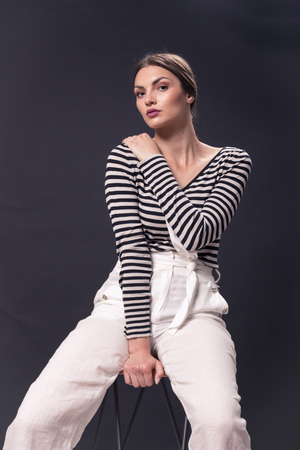 one young Caucasian woman 20s, 20-29 years, fashion model sitting bar stool, posing, studio, white background, horizontal stripe shirt, white pants, looking to camera, black and white image
