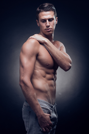 one young adult man, Caucasian, fitness model, muscular body, shirtless, jeans, black background, studio, posing, looking down bellow Stock Photo