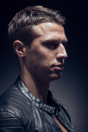 head and shoulders shot, one young adult man Caucasian, black background, studio, head headshot face, leather jacket, portrait Stock Photo