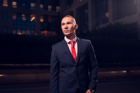 One young adult man, businessman, suit, formal wear, outdoors, night evening dark portrait modern building exterior