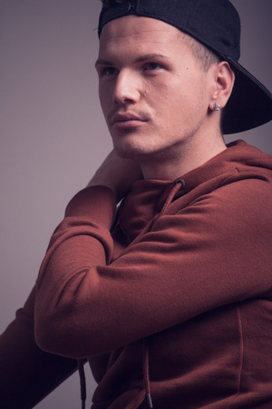 one young man, early 20s,  boyish looks, posing in studio, casual clothes, sweatshirt cap, upper body shot, looking sideways above