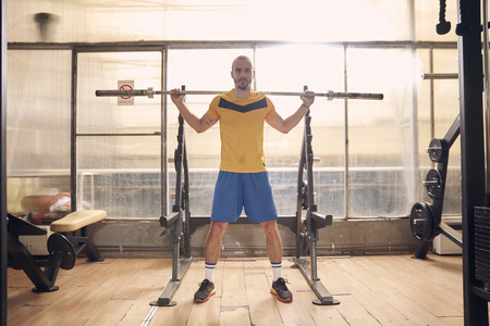 one young man, wearing sport clothes, about to do squat exercise with bar, in old beaten up gym interior. full lenght shot. Banco de Imagens