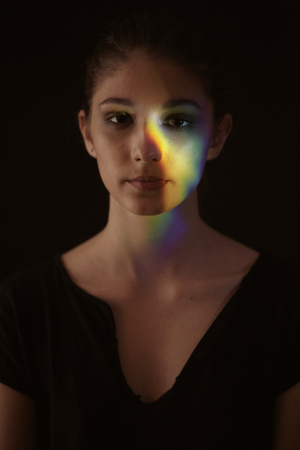 one girl portrait, face head, prism dispersion of light into colorful rainbow effect. black background.