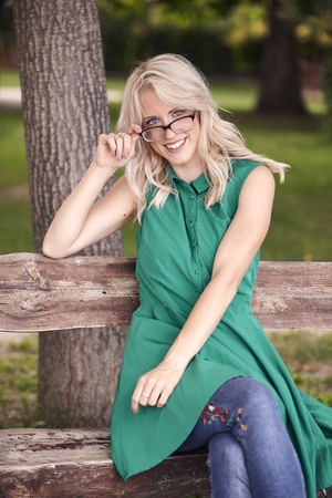 one young woman, 25 years old, sitting in wood bench in park, green dress,  happy positive portrait. holding eyeglasses, smiling. Stok Fotoğraf