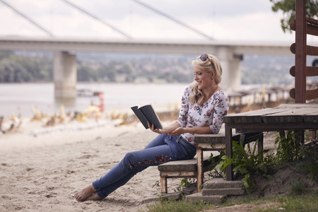 one young girl, sitting on steps on beach, summer, happy smiling, reading a book outdoors. side view. Stock Photo