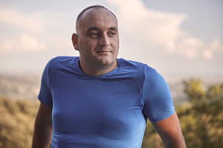 un hombre joven con sobrepeso, de 30 a 35 años, mirando de reojo, tiro de la parte superior del cuerpo. naturaleza al aire libre.
