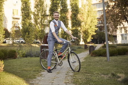one young smiling man, 20-29 years old,  wearing hipster suit, smart casual, posing sitting on a old city bike in park road trail.