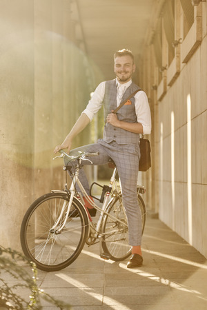 one young man, 20-29 years old,  wearing hipster suit, smart casual, posing sitting on a old city bike, sunny day, lens flare,