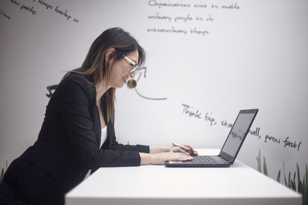 one young smiling woman, 30-39 years old, side view, upper body shot. working on laptop. wall with creative quotes  behind.