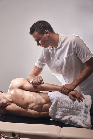 two young man, 20-29 years old, sports physiotherapy indoors in studio, photo shoot. Therapist masseur massaging arm of muscular patient laying on his side, with elbow.