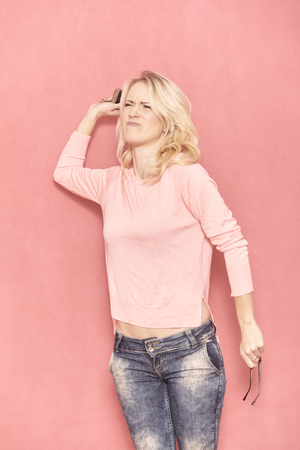 one young woman angry, throwing her smart phone, 20-29 years old, long blond hair. Shot in studio on pink background.