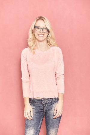 une jeune femme souriante, posant et attendant avec impatience la caméra, avec ses lunettes inclinées, 20-29 ans, longs cheveux blonds. Tourné en studio sur fond rose.