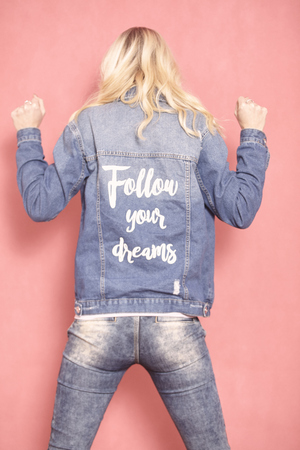 one young woman, 20-29 years old, long blond hair. Shot in studio on pink background. Wearing jeans jacket with sign follow your dreams on her back, (rear view). 写真素材