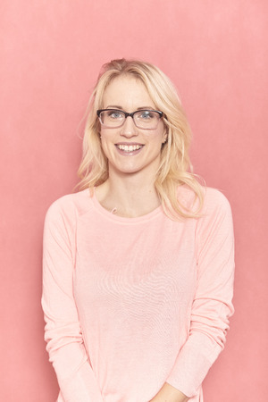 one young woman smiling portrait, looking to camera, wearing her glasses, 20-29 years old, long blond hair. Shot in studio on pink background.