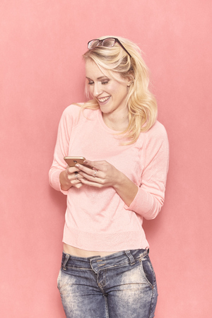 one young woman smiling, looking to camera, while texting or using her smartphone, 20-29 years old, long blond hair. Shot in studio on pink background.