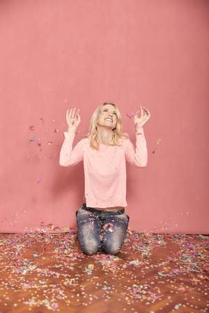 one young smiling woman portrait, looking to camera, kneeling on floor surrounded with falling confetti, 20-29 years old, long blond hair. Shot in studio on pink background. 版權商用圖片