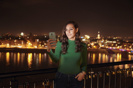 one young beautiful woman, 20-25 years old, looking at smart-phone. upper body shot. night time, dark, city scape behind in background (blurry, out of focus).