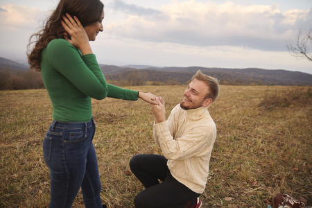 Young man kneeling proposing to young woman, his fiancee. Romantic couple age range of 20-29 years old, alone on mountain hill, in yellow Autumn grass field. National park