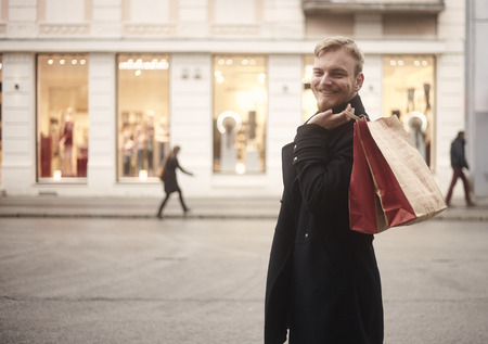 one young smiling and happy man, 20-29 years old, handsome and stylish, looking to camera while holding two shopping bags on his back. Pedestrians walking in background, store fronts windows included. Stok Fotoğraf