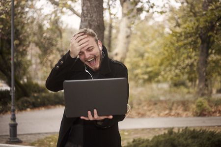 one young laughing man, can't believe it, while he is candidly gesturing putting his palm on his forehead. holding laptop in hand, communicating over Internet video call, could be family. Stock fotó