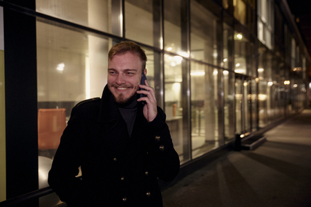 night time, one young smiling and happy man, 20-29 years, talking over his phone, standing in Autumn coat on street, in front of business offices windows outdoors.