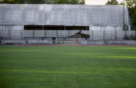 one young woman, small tiny in shot, running alone on a sports and field, running tracks. Large grass field (from football court). Foto de archivo