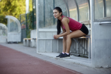 one young woman, 20-29 years, resting while sitting on a bench at sports court outdoors (track and field). 스톡 콘텐츠