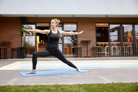 one young lady,20-29 years, old doing yoga on a yoga matt in a backyard of a beautiful fancy house. Stock Photo