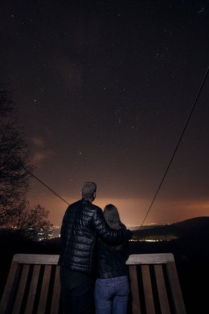 landscape shot, young couple starring in stars in night time, far in nature wilderness. Astrophotography
